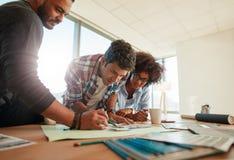 Diseñadores jovenes que trabajan junto en un proyecto creativo imagen de archivo libre de regalías
