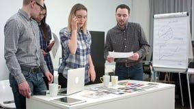 Diseñadores que hablan en el teléfono con el cliente mientras que selecciona colores de la paleta almacen de video