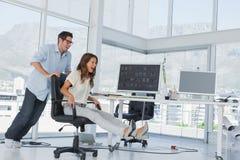 Diseñadores que se divierten con una silla de eslabón giratorio Imágenes de archivo libres de regalías