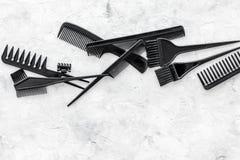 Diseñar el pelo con los peines y las herramientas en barbería en la maqueta de piedra de la opinión superior del fondo Fotos de archivo