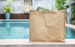 Diseñe el bolso del yute sobre fondo borroso de la piscina Imágenes de archivo libres de regalías