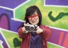 Diseñe a la muchacha adolescente con la cámara que coloca la pared cercana de la pintada Fotos de archivo libres de regalías