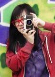 Diseñe a la muchacha adolescente con la cámara que coloca la pared cercana de la pintada Imágenes de archivo libres de regalías