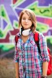 Diseñe a la muchacha adolescente con la mochila que coloca la pared cercana de la pintada. Fotografía de archivo