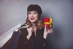 Diseñe a la muchacha del pelirrojo en sombrero con los panieres y la caja de regalo foto de archivo