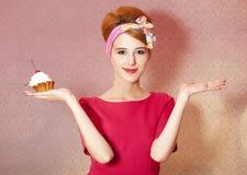 Diseñe a la muchacha del redhead con la torta en el fondo rosado. Imágenes de archivo libres de regalías