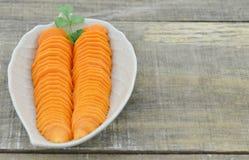 Diseñe la placa con las zanahorias cortadas en la tabla de madera, primer Imagenes de archivo
