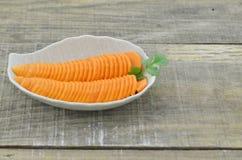 Diseñe la placa con las zanahorias cortadas en la tabla de madera, primer Fotos de archivo