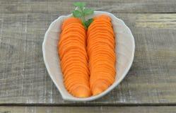 Diseñe la placa con las zanahorias cortadas en la tabla de madera, primer Fotografía de archivo libre de regalías