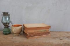 Diseñe la taza de café del vintage, lámparas de keroseno, libros viejos en la madera Foto de archivo libre de regalías