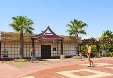 Diseño arquitectónico de un hotel turco con un restaurante chino, las palmeras y la gente relajándose en el verano fotos de archivo libres de regalías