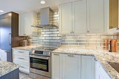Diseño blanco moderno de la cocina con el backsplash de plata imagenes de archivo