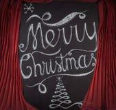 Diseño de letras dibujado mano de la Feliz Navidad enmarcado por curtai rojo Imagenes de archivo