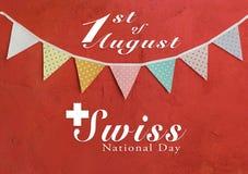 Diseño de tarjeta suizo del día nacional en banderas del partido del color en la pared roja del cemento Imagenes de archivo