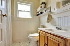 Diseño del cuarto de baño en colores cremosos con el gabinete de madera marrón y la pequeña ventana Imagen de archivo