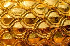 Diseño del estuco del oro de estilo tailandés nativo en la pared Imágenes de archivo libres de regalías