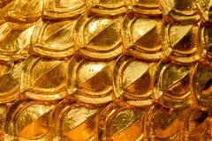 Diseño del estuco del oro de estilo tailandés nativo en la pared Foto de archivo libre de regalías