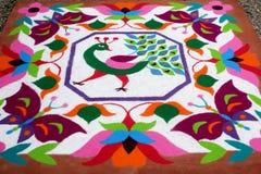 Diseño floral tradicional colorido de Rangoli hecho con colores pulverizados secos con el pavo real, las flores y las mariposas Imagenes de archivo