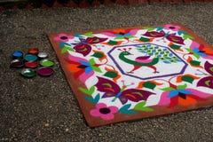 Diseño floral tradicional colorido de Rangoli hecho con colores pulverizados secos con el pavo real, las flores y las mariposas Imagen de archivo