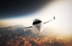 Diseño genérico de lujo brillante blanco Jet Flying privada de la foto en cielo bajo superficie de tierra Puesta del sol del fond Foto de archivo