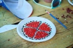 Diseño hecho a mano de una placa plástica con las semillas coloreadas en rojo y blanco Imágenes de archivo libres de regalías