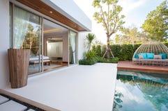 Diseño interior de lujo en el dormitorio del chalet de la piscina con la cama acogedora con el alto techo aumentado en la casa o  fotos de archivo