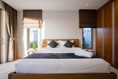 Diseño interior de lujo en el dormitorio del chalet de la piscina con la cama acogedora con el alto techo aumentado en la casa o  imágenes de archivo libres de regalías