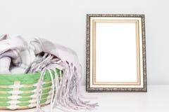 Diseño interior de Minimalistic con el marco de la foto y una cesta con ropa de lana caliente en un escritorio foto de archivo libre de regalías