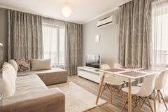Diseño interior moderno de la sala de estar brillante y acogedora con el sofá, la mesa de comedor y la cocina Apartamento-estudio fotos de archivo