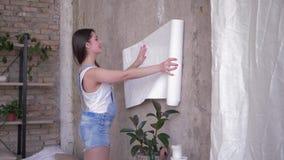 Diseño interior, retrato del dueño de casa de la mujer que desenrolla el nuevo papel pintado cerca de la pared durante reparaci almacen de metraje de vídeo