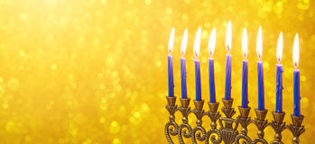 Diseño judío de la bandera del sitio web de Jánuca del día de fiesta con el menorah y velas sobre bokeh de oro Fotografía de archivo