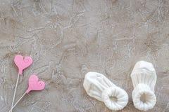 Diseño moderno de la fiesta de bienvenida al bebé con los zapatos en maqueta de piedra gris de la opinión superior del fondo Foto de archivo