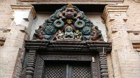 Diseño ornamental, entrada del templo De debajo entrada envejecida con la vieja escultura de madera colorida de dios sobre la ent metrajes