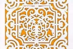 Diseño perforado floral blanco en tablero anaranjado Fotos de archivo libres de regalías