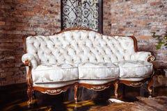 Diseño rico de lujo de la sala de estar con el sofá clásico elegante y la pared de ladrillo roja vieja foto de archivo libre de regalías