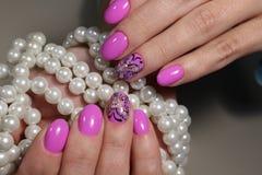 Diseño rosado de la manicura con la mariposa Foto de archivo libre de regalías