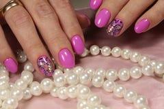 Diseño rosado de la manicura con la mariposa y los diamantes artificiales Fotos de archivo