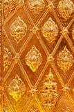 Diseño tailandés de oro del modelo en la pared del templo. Fotos de archivo