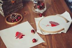 Diseños cruzados y decoraciones de la puntada de la Navidad en la tabla de madera Preparación de los regalos hechos a mano para e Imágenes de archivo libres de regalías