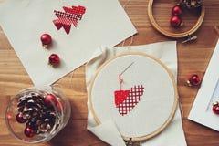 Diseños cruzados y decoraciones de la puntada de la Navidad en la tabla de madera Preparación de los regalos hechos a mano para e imagen de archivo