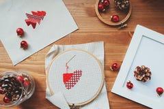 Diseños cruzados y decoraciones de la puntada de la Navidad en la tabla de madera Preparación de los regalos hechos a mano para e Foto de archivo libre de regalías