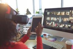 Dise?ador gr?fico de sexo femenino usando los dispositivos de las multimedias en el escritorio foto de archivo