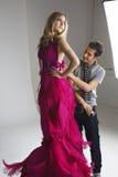 Diseñador de sexo masculino que ajusta el vestido en modelo de moda en estudio Imagenes de archivo