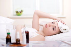 Disease. Sick woman resting in bed with focus to a glass of water and a blister pack of tablets and medication lying on the table alongside her bed Royalty Free Stock Photography