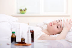 Disease. Sick woman resting in bed with focus to a glass of water and a blister pack of tablets and medication lying on the table alongside her bed Stock Photo