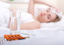 Disease. Sick woman resting in bed with focus to a glass of water and a blister pack of tablets and medication lying on the table alongside her bed Royalty Free Stock Image