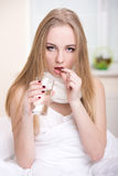 Disease. Young woman taking medicine in bedroom at home Royalty Free Stock Photos