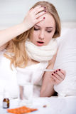 Disease. Woman with thermometer sick colds, flu, fever and migraine in bed Royalty Free Stock Image