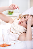 Disease. Woman with thermometer sick colds, flu, fever and migraine in bed Stock Photography