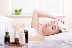 Disease. Sick woman resting in bed with focus to a glass of water and a blister pack of tablets and medication lying on the table alongside her bed Stock Photos